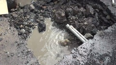A lot of water is coming through a pipe that is broken. Water leak on a road. Stock Footage