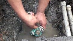 Hands of a worker that is repairing a pipe in a water leak. Stock Footage