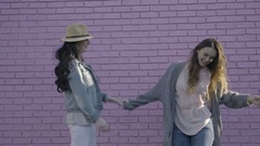 Young Women Practice Dance Moves Together In Front Of Pink Wall Stock Footage