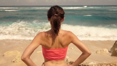Young woman on the beach looking at sea, super slow motion Stock Footage