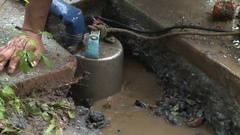 A worker is emptying the water left on the ground after a water leak. Stock Footage