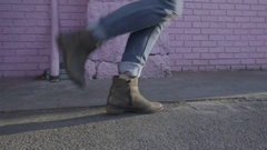 Profile Of Happy Young Women's Feet As She Dances In Front Of Pink Brick Wall Stock Footage