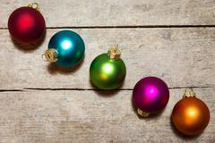 Five christmas balls on wooden background, in the colours red, orange, blue, gre Stock Photos