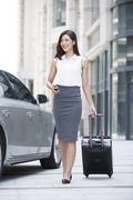 Confident businesswoman walking with wheeled luggage Stock Photos