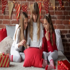 Triplets sisters dressed in xmas pajamas sitting in the bedroom having fun with Stock Footage