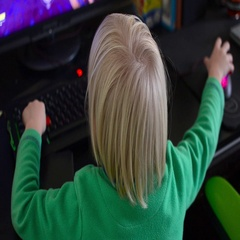 Child with white hair play ion the PC. Video from the back of kid. Stock Footage