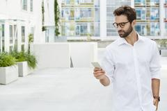 Dude in white shirt texting on Smartphone Stock Photos
