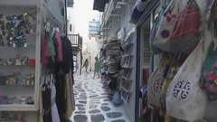 Gimbal shot walking down a narrow mykonos alley past shops Stock Footage