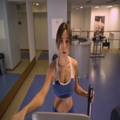 Lady trains in gym on cardio fitness equipment Stock Footage