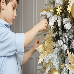 Portrait of little boy touches a toy on a Christmas tree Stock Footage