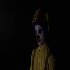 Scary clown with an axe in a dark room. Frightening jester, clown, buffoon Stock Footage