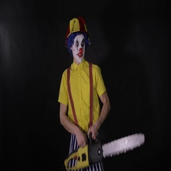 Scary clown with a chainsaw in the dark. Clown murderer threatening you Stock Footage