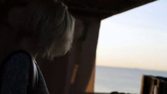 Beautiful blond girl walks smiling harmony near the beach at sunrise Stock Footage