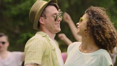 Cool guy in hat and mixed race girl laughing and dancing at open-air party Stock Footage