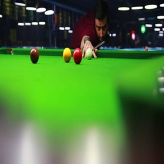 A low angle shot of a snooker player hitting the red ball, it goes in Stock Footage