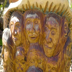 Wooden carvings of many faces of men and women Stock Footage