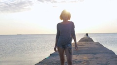 Blond girl walks smiling and happy near the beach at beautuful sunrise Stock Footage