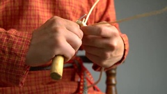 View of craftsman weaves basket using awl Stock Footage