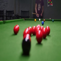 A shot behind the snooker balls and a young man tries to make the perfect shot Stock Footage