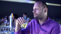 Happy handsome man drinking cocktail in the bar, during night, 4K Stock Footage