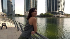 Pretty woman looking on the river in modern city, super slow motion Stock Footage