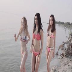 Three girls run and having fun at sea coast line at sunset. Stock Footage