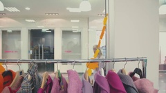 Two friends go shopping and go to the store clothing. Rail with coats Stock Footage