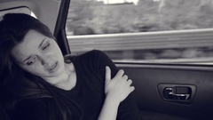 Sad woman crying in car black and white Stock Footage