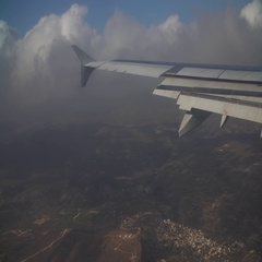 The wing of the plane on a background of clouds and land Stock Footage