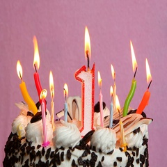 Anniversary 1 year with cake and candles on pink background Stock Footage