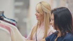 Two friends, blond and brunette, shopping and choosing clothes Stock Footage