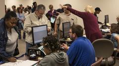 Poll worker points out voting terminals to male voter Stock Photos