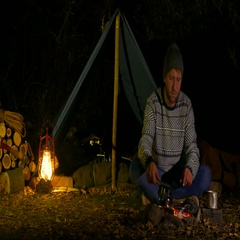 Traveler pouring coffee in old cup, sitting nera campfire. Arkistovideo
