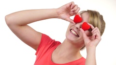 Woman holds red hearts over eyes having fun 4K Stock Footage