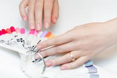 Girl chooses color of Polish for manicure. Stock Photos