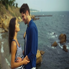Happy couple hugging each other , while standing on a beautiful stony beach Stock Footage