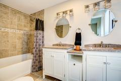 Bathroom detail. Vanity with dual sink and white cabinets Stock Photos