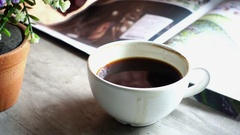 A man drinking a cup of hot black coffee (americano) and reading magazine Stock Footage