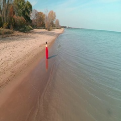 Lady in Red walking down beach Stock Footage