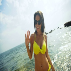 Attractive positive lady in a yellow swimming suit posing on the beach Stock Footage