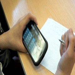 The student sitting at a desk holds a mobile phone Stock Footage