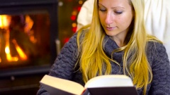 Young woman reading book at christmas time Stock Footage