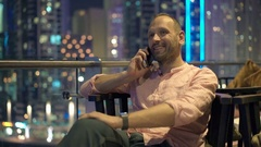 Young man talking on cellphone sitting on terrace in cafe at night Stock Footage