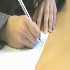 The schoolgirl writing the text in sheet of paper Stock Footage