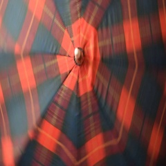 Red and blue checkered umbrella is  spinning Stock Footage