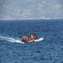 LESVOS, GREECE - NOV 2, 2015: Refugees in a rubber dinghy swim to shore from Stock Footage