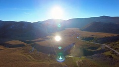 Aerial forward motion wide view mountain pastures autumn panorama sun reflection Stock Footage