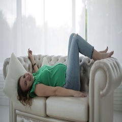The pregnant woman is lying on the sofa holding up her feet. Stock Footage