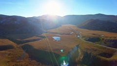 Mountain pastures aerial beautiful landscape grass horizon water pond blue sky Stock Footage
