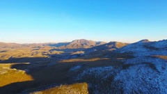 Beautiful scenery mountains range aerial hilly grass snow nature sunny blue sky Stock Footage